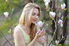 Blonde woman touching magnolia tree. stock photo