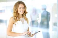 Blonde woman with touchpad computer looking at camera and smiling while business people shaking hands over background. Blonde woman with touchpad computer Royalty Free Stock Photos