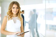 Blonde woman with touchpad computer looking at camera and smiling while business people shaking hands over background. Blonde woman with touchpad computer Royalty Free Stock Photography