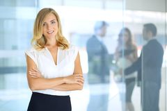 Blonde woman with touchpad computer looking at camera and smiling while business people shaking hands over background. Blonde woman with touchpad computer Stock Image