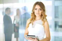 Blonde woman with touchpad computer looking at camera and smiling while business people shaking hands over background. Blonde woman with touchpad computer Stock Photography