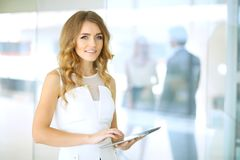 Blonde woman with touchpad computer looking at camera and smiling while business people shaking hands over background. Blonde woman with touchpad computer Royalty Free Stock Image