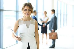 Blonde woman with touchpad computer looking at camera and smiling while business people shaking hands over background stock photography