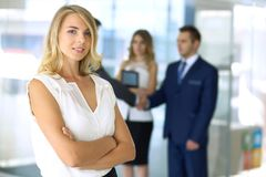 Blonde woman with touchpad computer looking at camera and smiling while business people shaking hands over background stock image