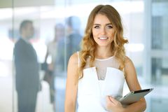 Blonde woman with touchpad computer looking at camera and smiling while business people shaking hands over background stock photos