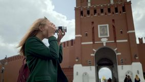 Blonde woman tourist taking pictures of Kremlin Moscow Russia Red Square. Rear view of a blonde young tourist wearing a green coat making photos of the Red stock footage