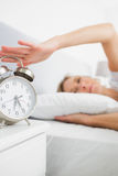 Blonde woman turning off her alarm in the morning Royalty Free Stock Image