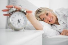 Blonde woman turning off ringing alarm clock Stock Image
