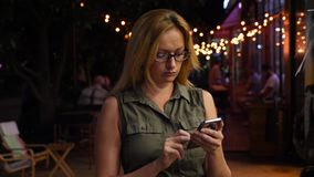 A blonde woman is typing a text message on a smartphone in the dark, in the summer. evening, night. 4k, slow motion.  stock footage