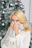 A blonde woman unwrapping colorfully packed New Year presents. The girl blonde covering the face with his own scarf, trying to hide his joy from others Royalty Free Stock Photos