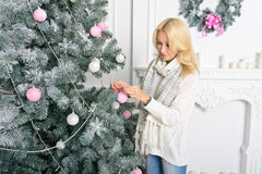 A blonde woman unwrapping colorfully packed New Year presents. Girl decorates the Christmas tree, toys white and pink Stock Image