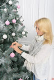 A blonde woman unwrapping colorfully packed New Year presents. Girl decorates the Christmas tree, toys white and pink Royalty Free Stock Photos