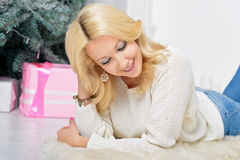 A blonde woman unwrapping colorfully packed New Year presents. Portrait of a young girl with a gift in New Year interior Stock Image