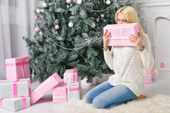 A blonde woman unwrapping colorfully packed New Year presents. A blonde woman unwraping colorfully packed New Year presents Royalty Free Stock Photography