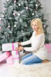 A blonde woman unwrapping colorfully packed New Year presents. A blonde woman unwraping colorfully packed New Year presents Stock Images