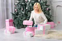 A blonde woman unwrapping colorfully packed New Year presents. A blonde woman unwraping colorfully packed New Year presents Stock Image