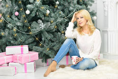 A blonde woman unwrapping colorfully packed New Year presents. A young girl with blonde hair is sitting with s cup of ginger tea near pile of presents under Royalty Free Stock Photos