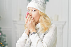 A blonde woman unwrapping colorfully packed New Year presents. Young girl in warm hat and sweater, breathing on the palm of her hand to warm up Stock Photos
