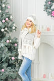 A blonde woman unwrapping colorfully packed New Year presents. Young girl in warm hat and sweater, standing next to a Christmas tree and smiling happily Stock Photos