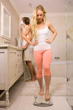 Blonde woman about use a weighing scale while her boyfriend shaving Stock Image
