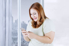 Blonde woman uses cellphone in apartment Royalty Free Stock Photography