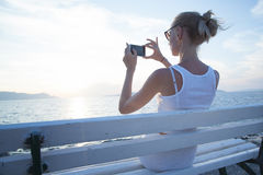 Blonde woman using cellphone on vacation. Stock Photo