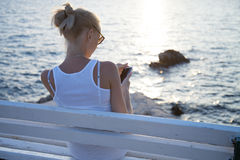 Blonde woman using cellphone on vacation. Royalty Free Stock Images