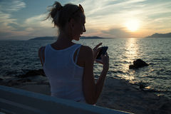 Blonde woman using cellphone on vacation. Royalty Free Stock Photos