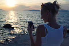 Blonde woman using cellphone on vacation. Royalty Free Stock Photo