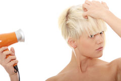 Blonde woman using hair drier Royalty Free Stock Photo