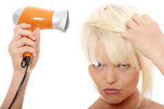 Blonde woman using hair drier Royalty Free Stock Photography