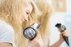 Blonde woman using hair dryer. Positive woman using hair dryer on her blonde hairdo. Haircare, hairstyling concept royalty free stock image
