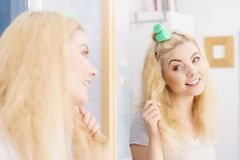 Blonde woman using hair rollers stock images