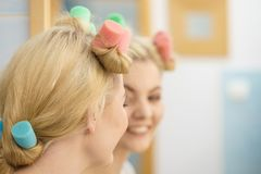 Blonde woman using hair rollers stock photo
