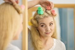 Blonde woman using hair rollers stock photos