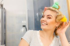 Blonde woman using hair rollers royalty free stock image