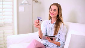 Blonde woman using her credit card and tablet pc Stock Photography