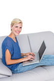 Blonde woman using her laptop on the couch Royalty Free Stock Photography