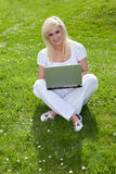 Blonde woman using a laptop on the grass Stock Photo
