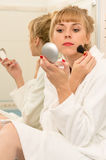 Blonde woman using mascara brush in bathroom Stock Images