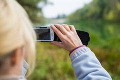 A blonde woman using a phone takes a photo of a landscape. Royalty Free Stock Images