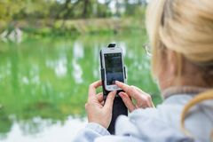 A blonde woman using a phone takes a photo of a landscape. Stock Photography