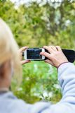 A blonde woman using a phone takes a photo of a landscape. Royalty Free Stock Photos