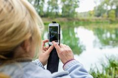 A blonde woman using a phone takes a photo of a landscape. Stock Image