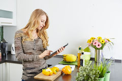 Blonde woman using a tablet computer to cook Royalty Free Stock Images