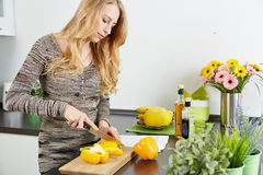 Blonde woman using a tablet computer to cook Stock Images
