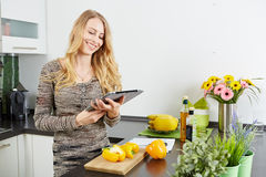 Blonde woman using a tablet computer to cook Royalty Free Stock Image