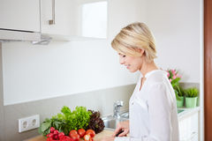 Blonde woman using a tablet computer to cook Royalty Free Stock Photo