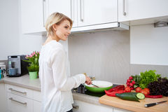 Blonde woman using a tablet computer to cook Stock Image