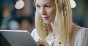 Blonde woman using tablet portrait.Corporate business team work office meeting.Caucasian businessman and businesswoman